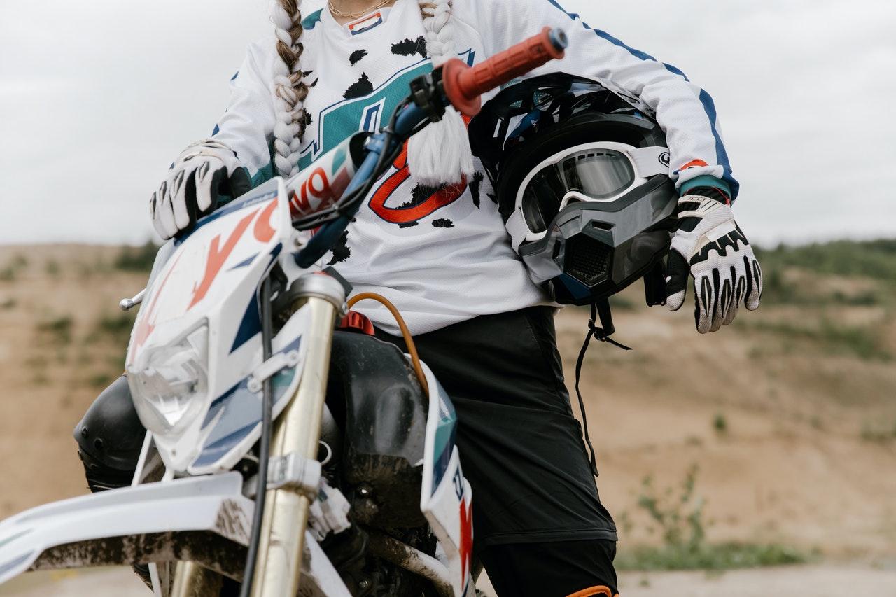 Motorradfahrerin mit Helm unter dem Arm