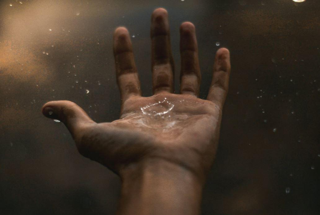 Regentropfen fallen in eine ausgestreckte Hand